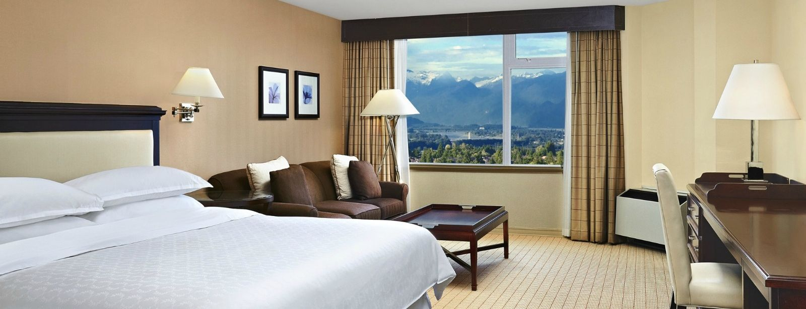 A Corner King Room overlooking the surrounding city and mountains at our Surrey, BC Hotel.